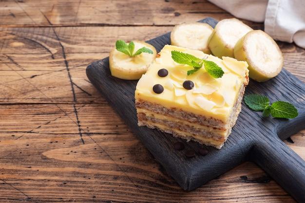 ナッツとチョコレートドロップのバナナスポンジケーキ。お茶、木製の背景のためのおいしい甘いデザート。上面図、コピースペース。