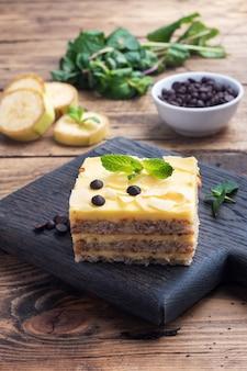 견과류와 초콜릿 방울과 바나나 스폰지 케이크. 차, 나무 배경에 대 한 맛있는 달콤한 디저트.
