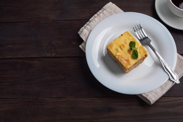 견과류와 민트 바나나 스폰지 케이크. 차 평면도를위한 맛있는 달콤한 디저트. 어두운 나무.