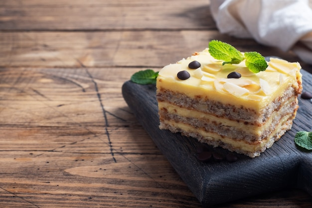 Banana sponge cake with nuts and chocolate drops. delicious sweet dessert for tea, wooden background. copy space