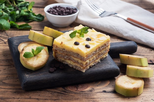 Banana sponge cake with nuts and chocolate drops. delicious sweet dessert for tea, wooden background. top view, copy space.