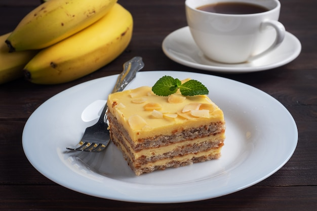 Banana sponge cake with nuts and mint. delicious sweet dessert for tea, dark wooden background.