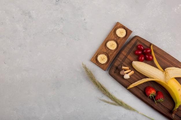 Банан, клубника и ягоды на деревянном блюде