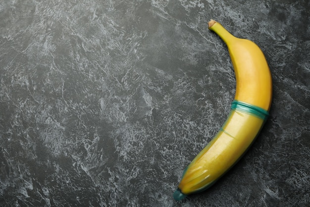 Banana with condom on black smokey background, space for text
