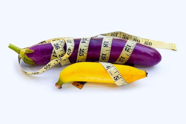 Банан с длинными фиолетовыми баклажанами, завернутый в измерительную ленту на белом фоне.
