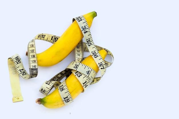 Банан, завернутый в измерительную ленту на белом фоне.