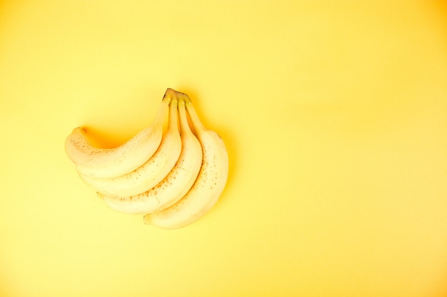Banana on yellow paper background