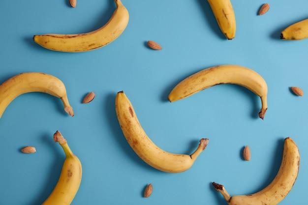 Banane e mandorle su sfondo blu. selezione di cibi sani per il cuore. fonte di vitamine, fibre alimentari e minerali. alimentazione sana e prodotti per dimagrire. ingredienti per la colazione