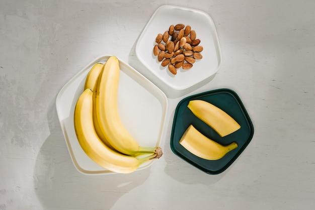Бананы и миска с ломтиками на сером фоне