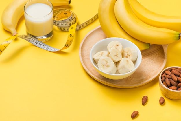 Бананы и миндаль с рулеткой на желтом фоне с копией пространства