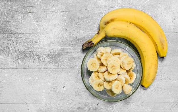 ガラス板のバナナとバナナのスライス。白い素朴な背景に
