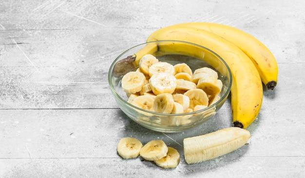 ガラスプレートのバナナとバナナスライス。白い素朴な背景に