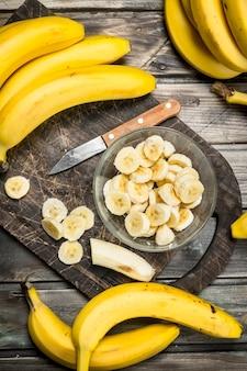 ナイフで黒いまな板のプレートにバナナとバナナのスライス。木製の背景に。