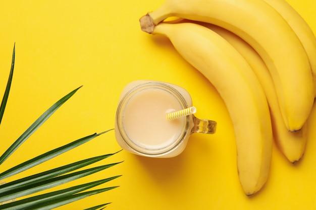 Бананы и сок на желтом фоне. свежие фрукты