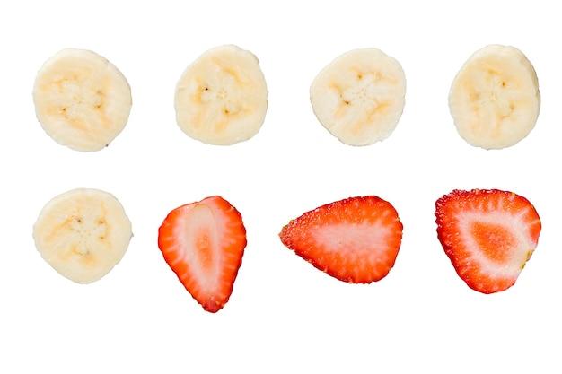 Кусочки бананов и клубники, изолированные на белом фоне.