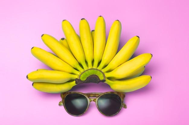 Бананы и солнцезащитные очки на розовом фоне.