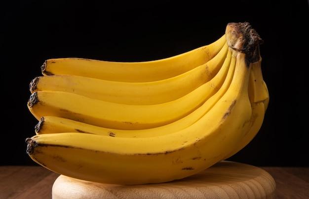 バナナ、丸い木の表面に置かれたバナナの束