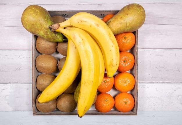 古い木の床の表面にある古い木製のトレイに置かれたバナナ、会議梨、みかん、キウイ