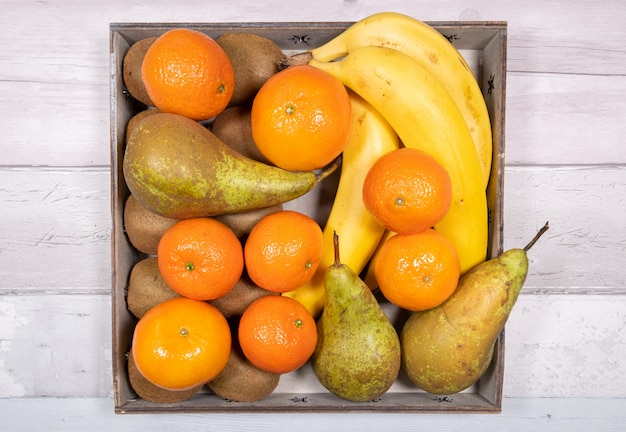 Bananas, conference pears, tangerines and kiwis placed in an old wooden tray on a surface of old wooden floor