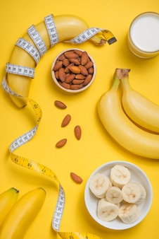 Bananas glass of milk and almonds with measuring tape on yellow background with copy space