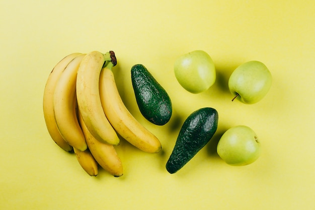 Bananas, green apple and avocado on a yellow background.