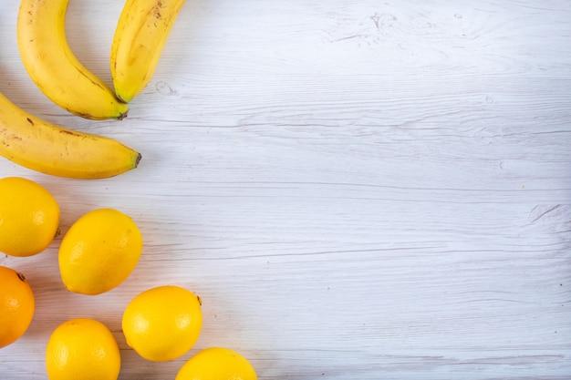 Banane e limoni vista dall'alto con spazio di copia sul tavolo bianco