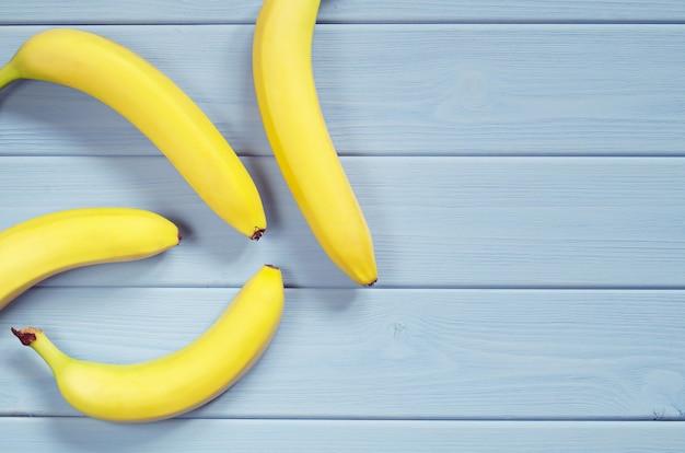 파란색 나무 테이블에 있는 바나나, 텍스트를 위한 공간이 있는 위쪽 보기