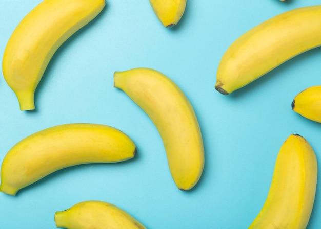 色付きの背景にバナナ。純粋な青の背景に黄色の新鮮なバナナのパターン。