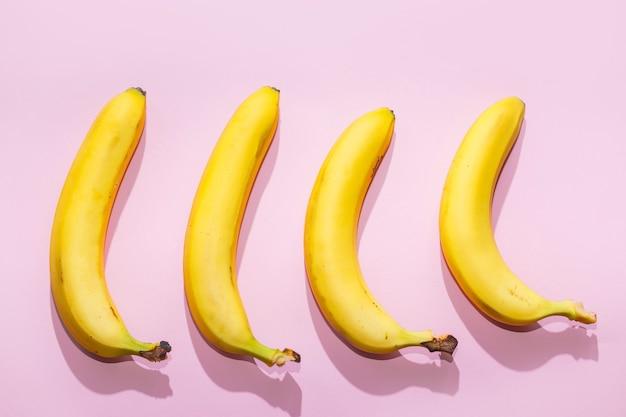 Бананы на розовом фоне пастельных тонов. концепция еды минимальная идея