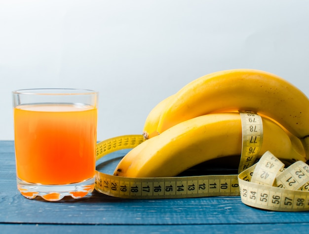 Bananas and orange juice on a wooden . food for weight