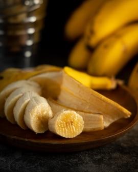 Бананы подаются на столе с черным фоном и деревянной тарелкой