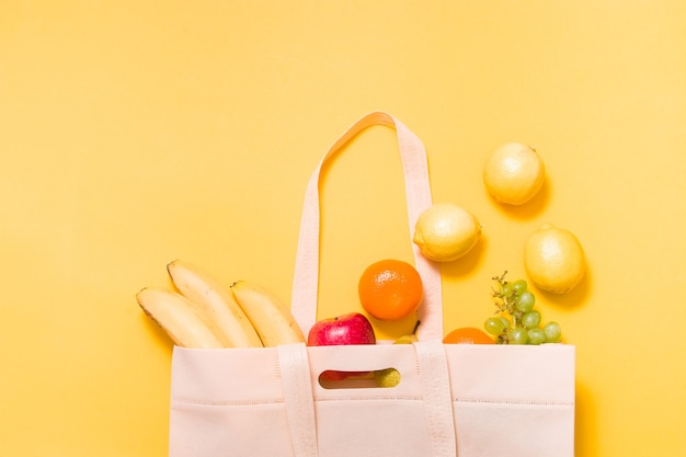Bananas, tangerines, grapes, apple, pear and lemons in a fabric shopping bag on yellow surface