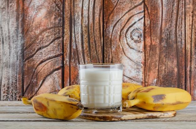 Banane con vista laterale del latte su legno e tagliere