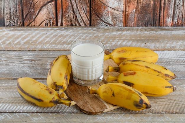 Banane con latte su legno e tagliere, alta veduta.