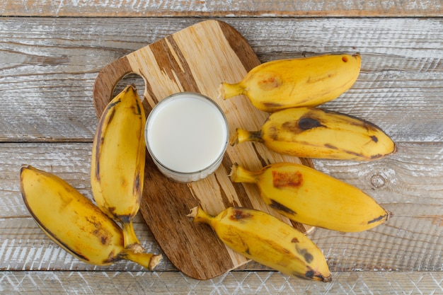 Bananas with milk on wooden and cutting board,