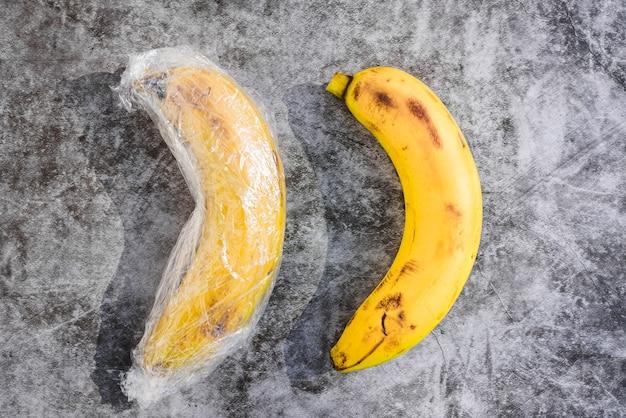 無意味なプラスチック包装で包まれた自然な皮のバナナ