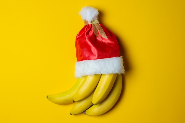 Bananas on yellow background in santa claus hat