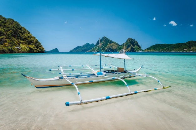 Banca boat in blue lagoon with beautiful mountains in background. el nido, palawan, philippines