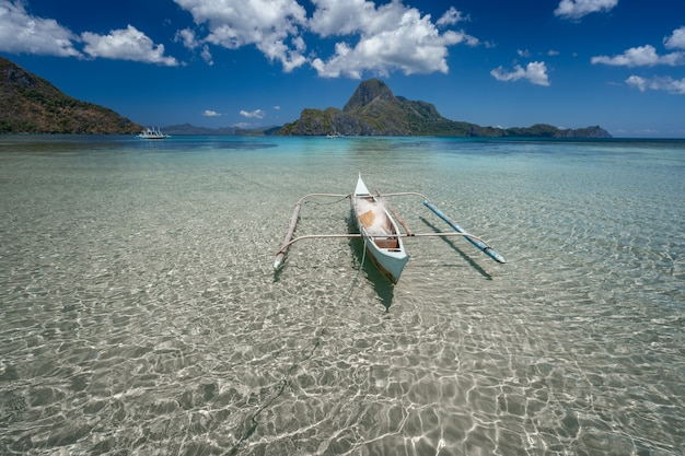 Banca boat in crystal clear shallow water with tropical island in background. el nido, palawan, philippines.