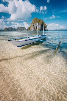 Banca boat on sandy beach in el nido, palawan, philippines
