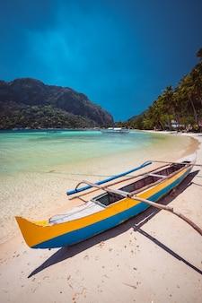 Banca boat on sandy tropical beach. el nido, palawan island, philippines.