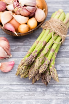 Banches of fresh green asparagus, garlic on wooden table