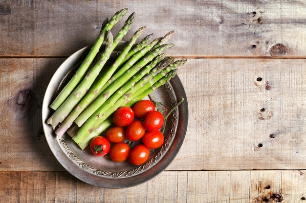Banches of fresh green asparagus and tomatoes in a metall plate on wooden background