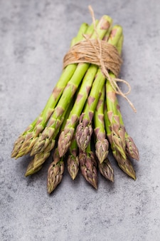 Banches of fresh green asparagus and vegetables on wooden table