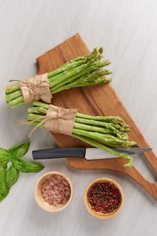 Banches of fresh green asparagus on wooden surface