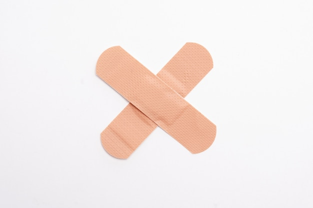 Band-aids forming an x or a cross on white