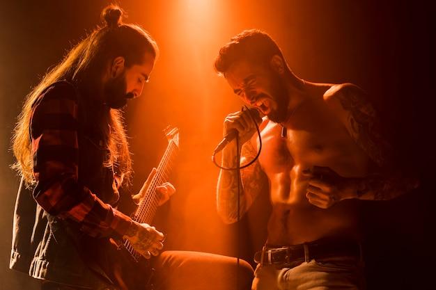 ギタリストとボーカリストと一緒にステージでバンドを組む