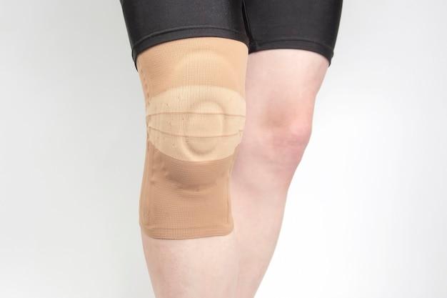 Повязка для фиксации травмированного колена ноги человека на белом фоне.