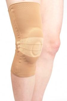 인간 다리의 다친 무릎을 흰색에 고정시키는 붕대