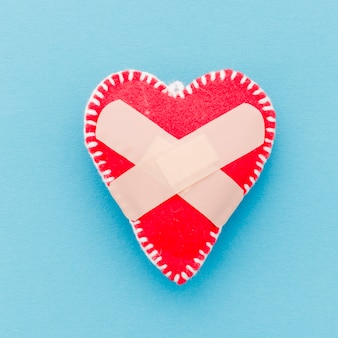 Bandage over the white stitch red heart shape on blue background